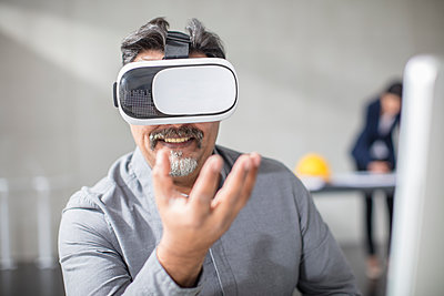 Man wearing VR glasses in office - p300m1550127 by zerocreatives
