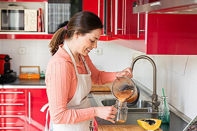 Beautiful woman pouring smoothie to mason jar in kitchen at home - p300m2264460 by VITTA GALLERY