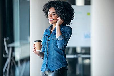 Happy female customer service representative having coffee while talking through headphones in office - p300m2275583 by Josep Suria