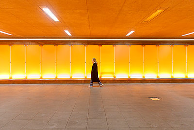 Young woman walking through underpass in Arlanda Airport, Sweden - p352m2119989 by Åke Nyqvist