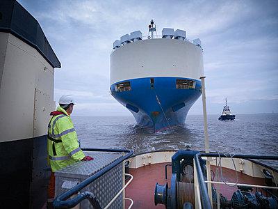 Worker standing on deck of tugboat - p429m747057f by Monty Rakusen