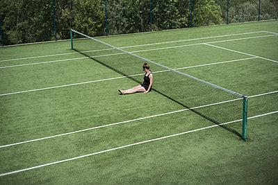 Frau sitzt am Boden auf einem Tennisplatz - p966m1514950 von Tobias Leipnitz