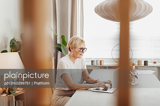 Woman using laptop at home - p312m2299751 by Plattform