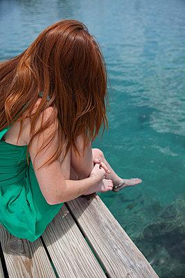 Rothaarige Frau am Steg ruht sich aus - p045m1573692 von Jasmin Sander