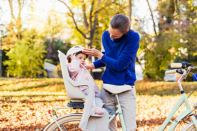 Mother and daughter riding bicycle, baby wearing helmet sitting in children's seat - p300m2059895 by Daniel Ingold
