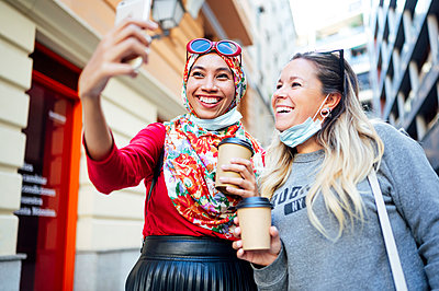 Female friends taking selfie while holding coffee cups in city during COVID-19 - p300m2240981 by Jose Luis CARRASCOSA