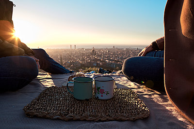 Gay men with coffee cups sitting on observation point against clear sky, Bunkers del Carmel, Barcelona, Spain - p300m2256683 by Veam