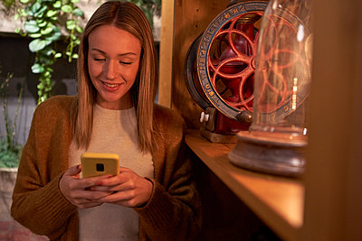 Smiling woman text messaging on smart phone in cafe - p300m2257376 by Veam