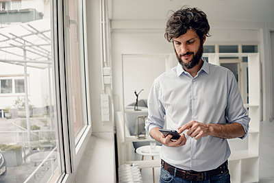 Young man using his smartphone - p586m1562040 by Kniel Synnatzschke