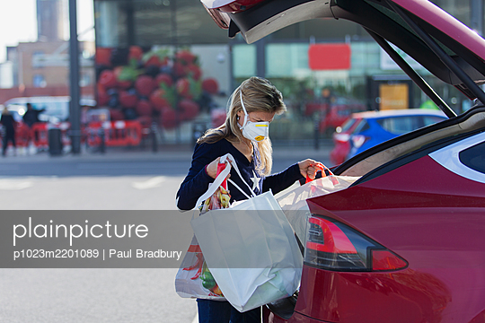 Woman with face mask loading groceries into car in parking lot - p1023m2201089 by Paul Bradbury