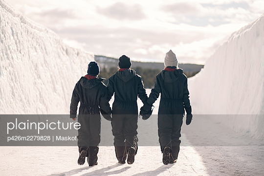Full length rear view of mother holding hands of son and daughter while walking on snow during winter - p426m2279828 by Maskot