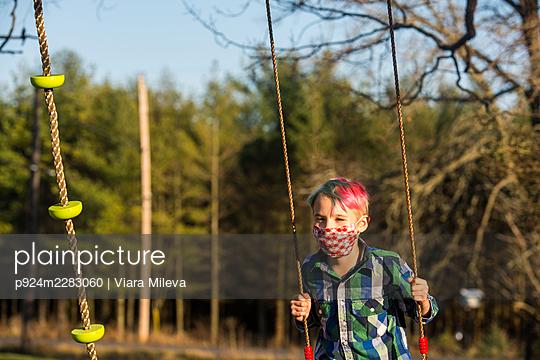 Canada, Ontario, Boy in face mask on swing - p924m2283060 by Viara Mileva