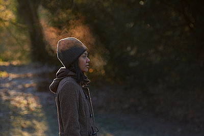Side profile of Asian woman enjoying the cold weather blowing mist - p1166m2112886 by Cavan Images