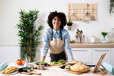 Curly woman preparing a vegan sandwich with avocado, cucumber, rocket salad and tomato - p300m2240596 von Giorgio Fochesato