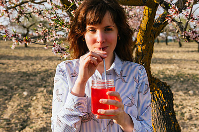 Young woman drinking strawberry soda at almond tree - p300m2276006 by Mar