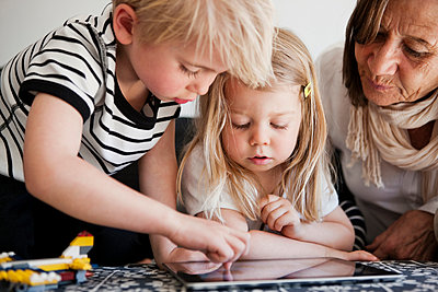 Grandmother with grandchildren using digital tablet - p312m1075904f by Peter Rutherhagen