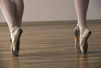 Two ballet dancers standing on tiptoes, low section, close-up - p4340223f by Oscar Knott