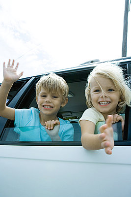 Children sticking heads out of car window - p62316455f by Sigrid Olsson