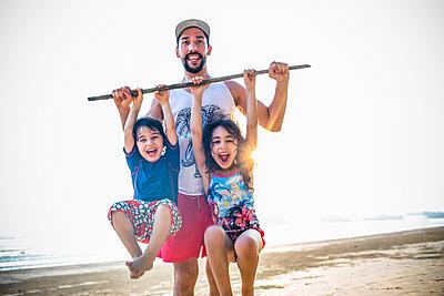 Father and children on beach, portrait - p680m1511704 by Stella Mai