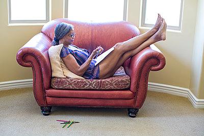 Side view of woman with legs raised on armchair drawing in notebook - p924m1174896 by Deborah Kolb