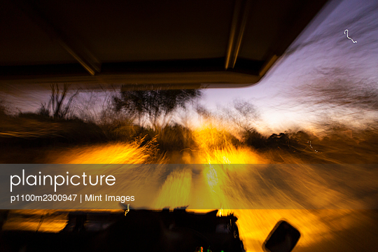 Vehicle with lights moving along a road after sunset.  - p1100m2300947 by Mint Images