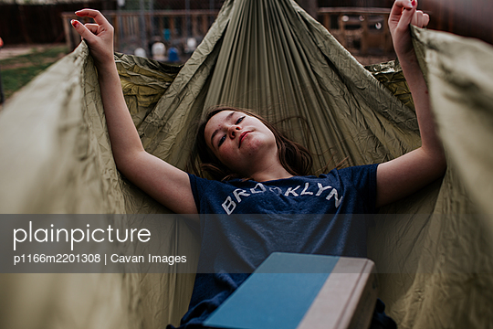 Teen girl laying in hammock with a book - p1166m2201308 by Cavan Images