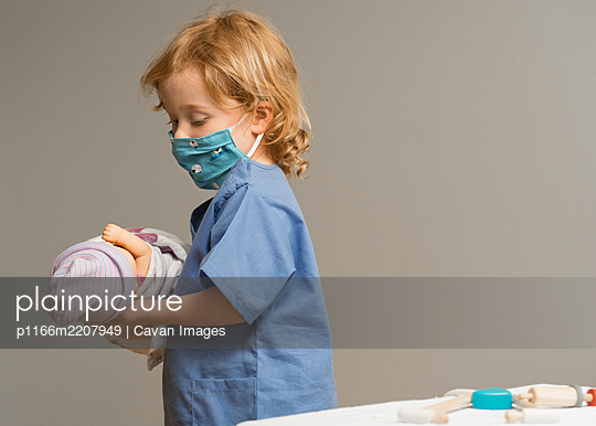 young child wearing medical PPE holds a swaddled baby doll - p1166m2207949 by Cavan Images