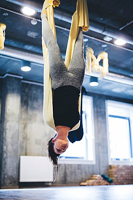 Young woman practicing aerial yoga while hanging from hammock in gym - p1166m1576474 by Cavan Images