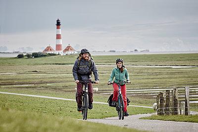 Pärchen mit Trekking-Bikes in Sankt Peter-Ording und am Westerhever Leuchtturm - p300m1416704 von Roger Richter