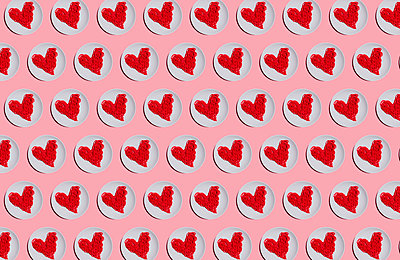 Pattern of plates with red-colored heart-shaped spaghetti against pink background - p300m2198263 by Gemma Ferrando