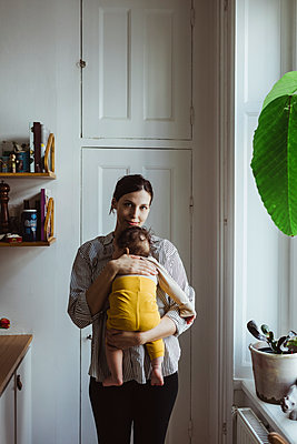 Portrait of mother carrying baby boy while standing in kitchen - p426m2279899 by Maskot