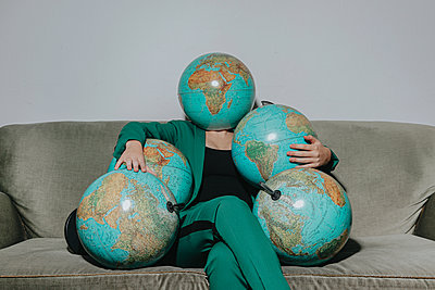 Woman on a sofa holding several globes - p750m2192500 by Silveri