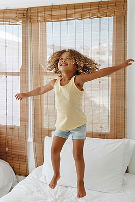 Little girl jumping with arms open on bed in beach house - p924m2138503 by Image Source
