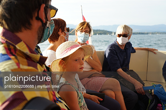 A small girl on a boat trip with her masked family - p1610m2208688 by myriam tirler