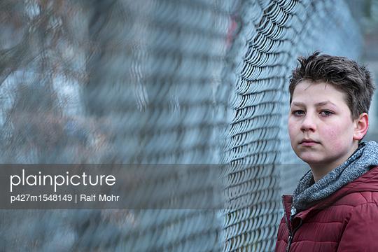 Junge an einem Drahtzaun - p427m1548149 von R. Mohr