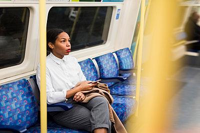 UK, London, businesswoman with cell phone sitting in underground train - p300m1581652 von Mauro Grigollo