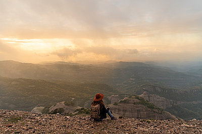Woman with backback, sitting on mountain, looking at view - p300m2078995 von VITTA GALLERY