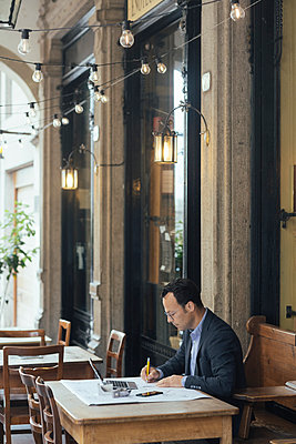 Businessman at work in a coffee shop - p300m2113983 by Alberto Bogo