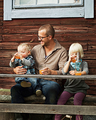 Father with two kids drinking juice in front of wooden house - p312m670277f by Matilda Lindeblad