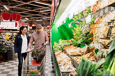 Couple choosing vegetables while using phone in supermarket - p426m1148161 by Maskot