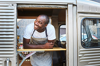Smiling mid adult male owner looking away while standing in food truck - p426m1536949 by Maskot