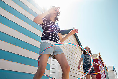 Girls hoola hooping by beach huts, Southwold, Suffolk, UK - p429m1181114 by Seb Oliver