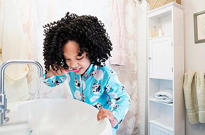 African American girl brushing teeth in bathroom - p555m1311743 by JGI/Tom Grill