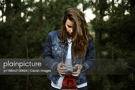 Woman with camera looking away while standing against pine trees - p1166m2130624 by Cavan Images
