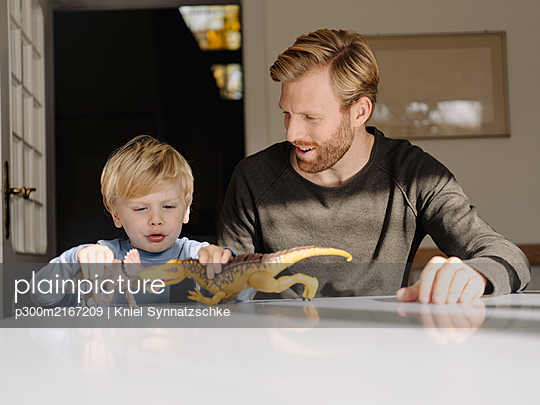 Father and son playing with dinosaur figures at home - p300m2167209 by Kniel Synnatzschke