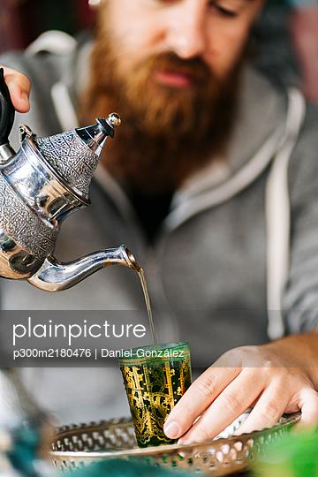 Man pouring tea into green glass - p300m2180476 by Daniel González