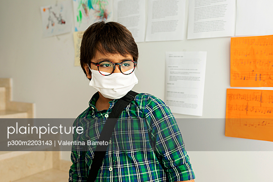 Boy wearing mask looking away while standing against wall in school - p300m2203143 by Valentina Barreto