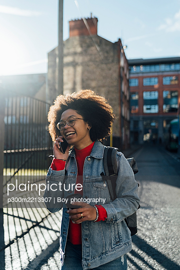 Cheerful afro woman talking over smart phone while standing with coffee cup on street - p300m2213907 by Boy photography