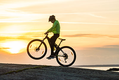 Boy cycling on beach at sunset - p312m1556963 by Mikael Svensson
