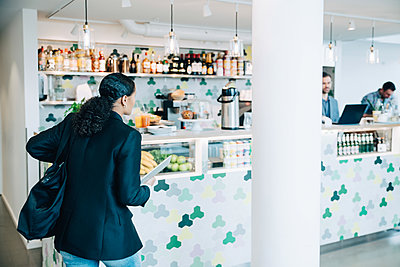 Businesswoman with laptop walking towards checkout counter in cafe - p426m2159350 by Maskot
